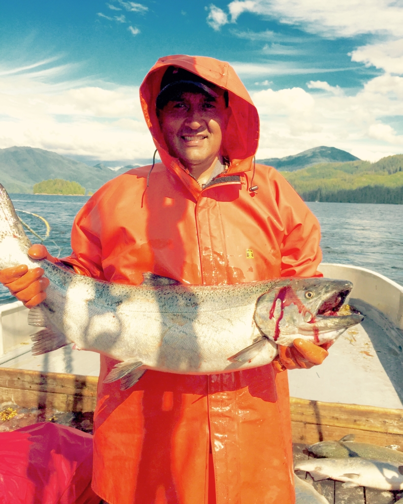 man in orange rainsuit holds king salmon